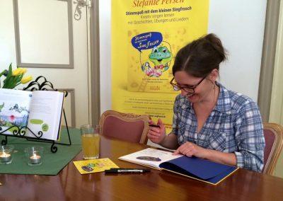 Illustratorin signiert bei der Singfrosch Präsentation