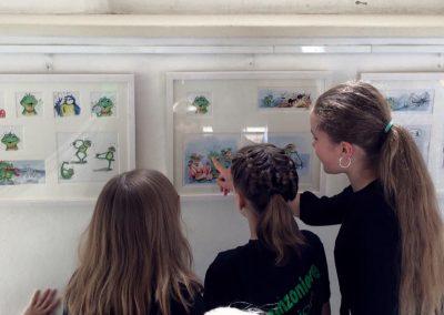 Kinder schauen Zeichnungen vom Singfrosch an