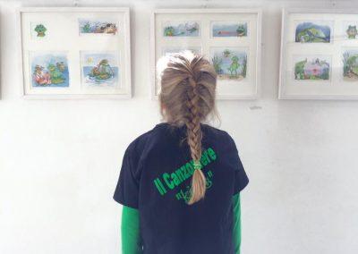 Kind betrachtet Zeichnungen auf Singfrosch Präsentation