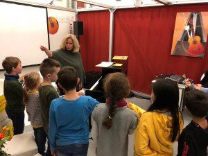 stefanie Fersch unterrichtet Singkinder auf dem Breitkopf Härtel Messestand